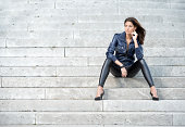 Beautiful woman in a fashionable outfit sitting on stone stairs. Nikon D800e. Converted from RAW (XXXL)