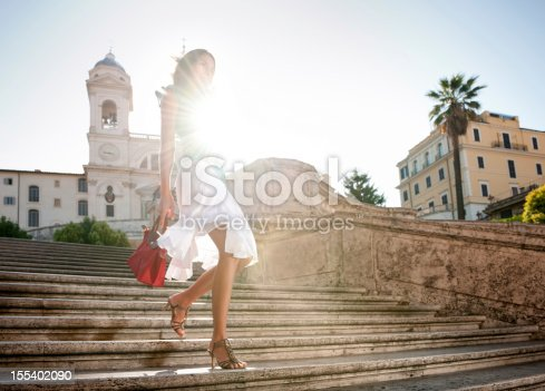 Beautiful model in dapper summer fashion walking down the famous Spanish steps in Rome, Italy with the sun rising in back. Nikon D3X. Converted from RAW.