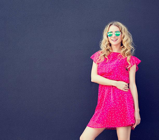 summer fashion woman in pink dress at dark wall - sommer teenagermode stock-fotos und bilder