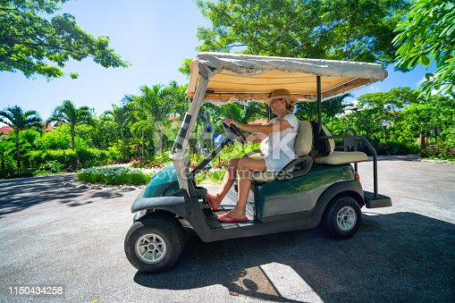 side view happy smiling woman in white dress driving with golf cart in luxury island resort on sunny vacation day