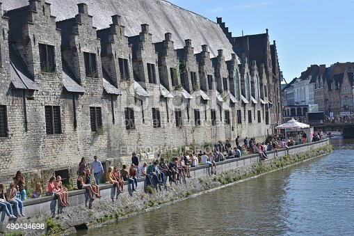 Ghent, Belgium – July 18, 2015:  Summer Festival in Olf City of Ghent. People enjoy sun weather seating on the bank of the river Leie