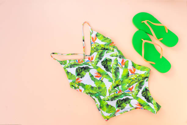 Summer flat lay scenery with swimsuit Summer flat lay scenery with swimmimg suit and sandals on pink background with copy space swimwear stock pictures, royalty-free photos & images