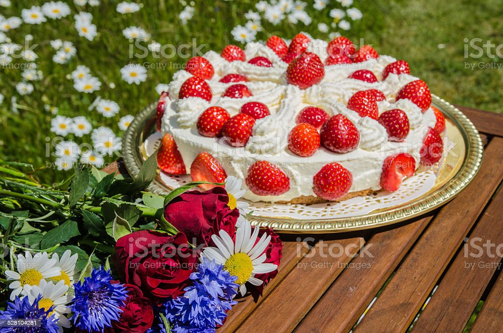 Summer flowers at a table with a homemade strawberry cake stock photo