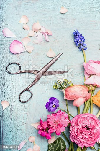 istock Summer flowers bunch making with various colorful flowers from garden and shears on blue vintage shabby chic background 890763844