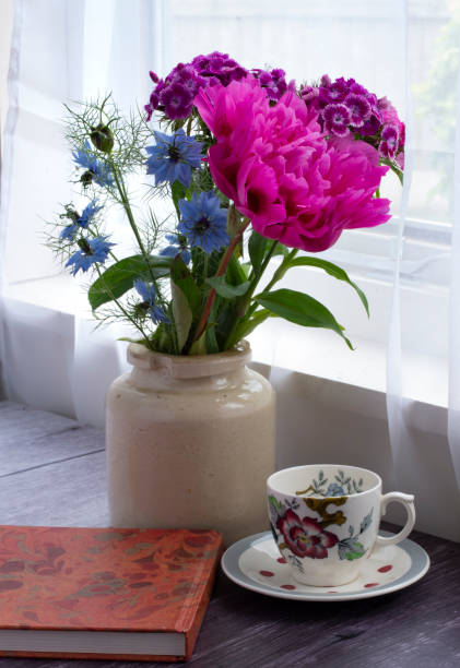 Summer flowers in a vase by a window stock photo