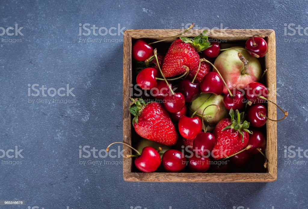 Summer Food Background. Wooden box with apples, strawberries and cherry on blue concrete table Copy space, top view royalty-free stock photo