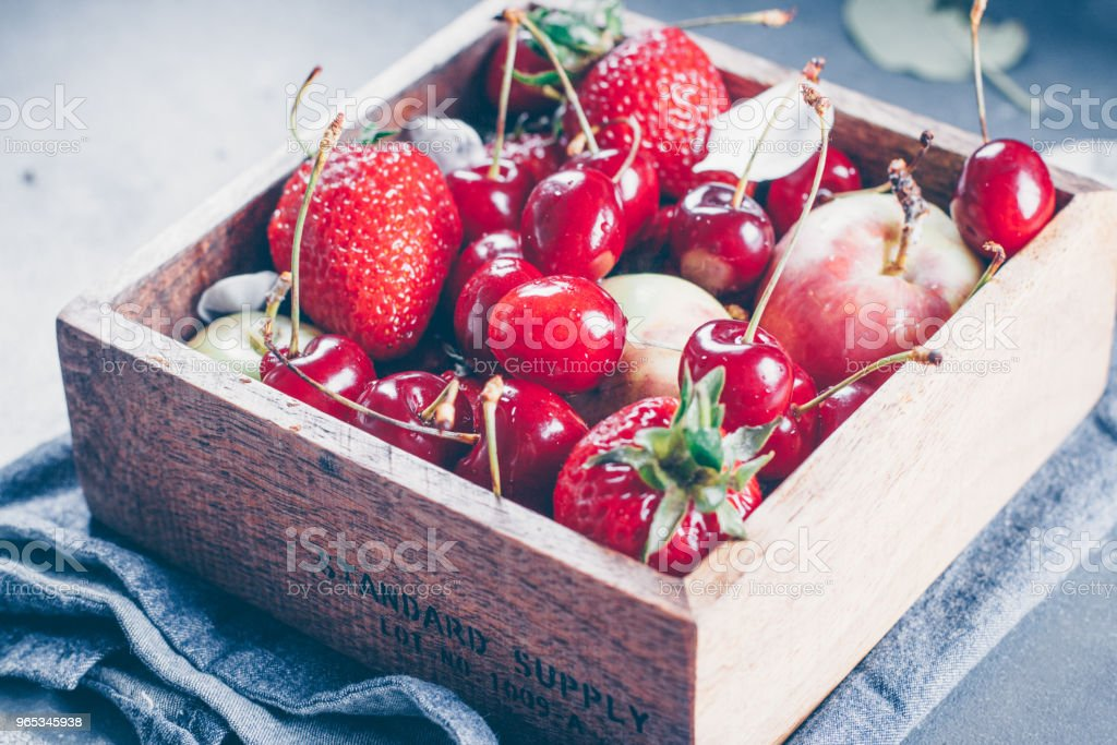 Summer Food Concept. Fresh mix of berries - strawberry, cherry and apples in a wooden box on blue denim background. Copy space royalty-free stock photo