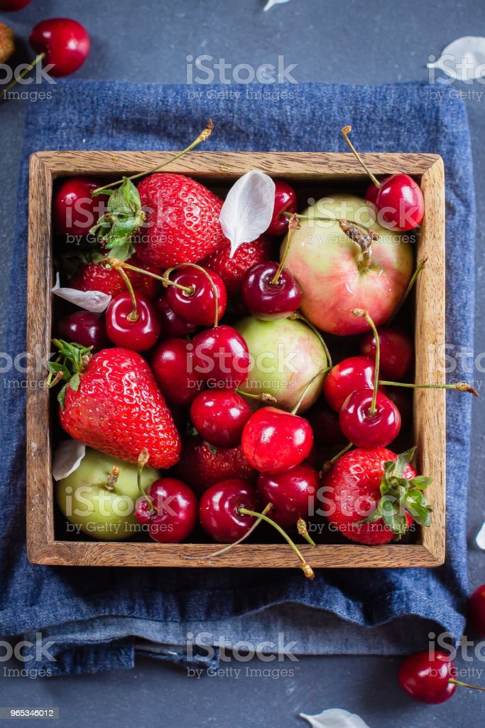 Summer Food Concept. Fresh mix of berries - strawberry, cherry and apples in a wooden box on blue denim background. Copy space, Top view royalty-free stock photo