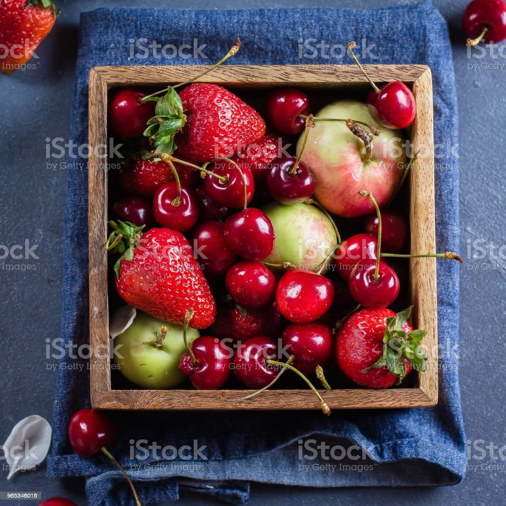 Summer Food Concept. Fresh mix of berries - strawberry, cherry and apples in a wooden box on blue denim background. Copy space, Top view zbiór zdjęć royalty-free