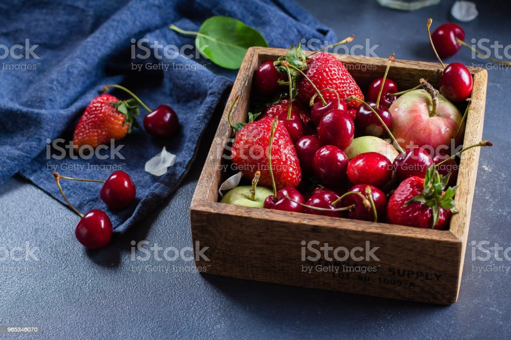 Summer Food Concept. Fresh mix of berries - strawberry, cherry and apples in a wooden box on blue denim background. Copy space zbiór zdjęć royalty-free