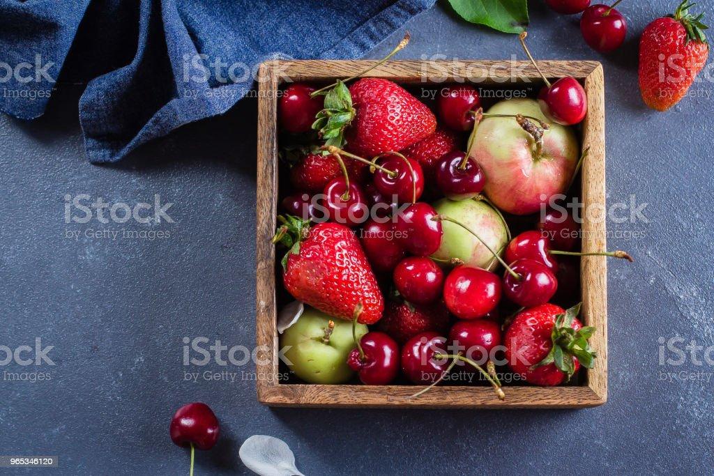 Summer Food Concept. Mélange frais de petits fruits - fraise, cerises et pommes dans une boîte en bois sur fond bleu denim. Copie espace, vue de dessus - Photo de Aliment libre de droits