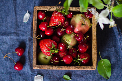 Summer Food Concept Fresh Mix Of Berries Strawberry Cherry And Apples In A Wooden Box On Blue Denim Background Copy Space Top View Stock Photo - Download Image Now