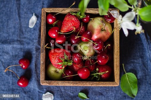 Summer Food Concept Fresh Mix Of Berries Strawberry Cherry And Apples In A Wooden Box On Blue Denim Background Copy Space Top View Stock Photo & More Pictures of Apple - Fruit