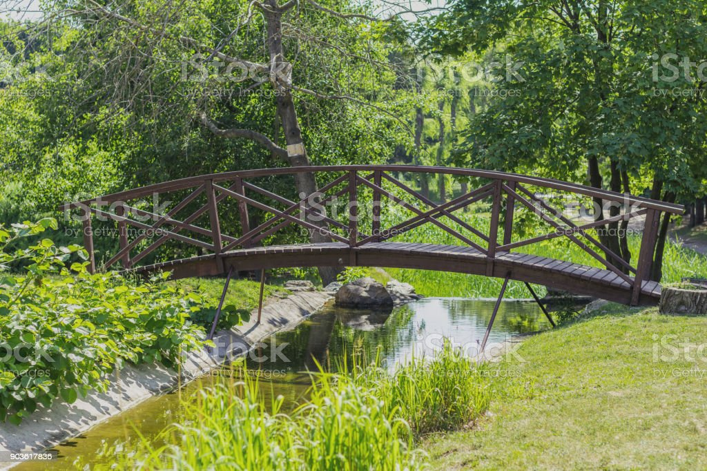 Summer footpath in the city park with a bridge on a sunny day royalty-free stock photo