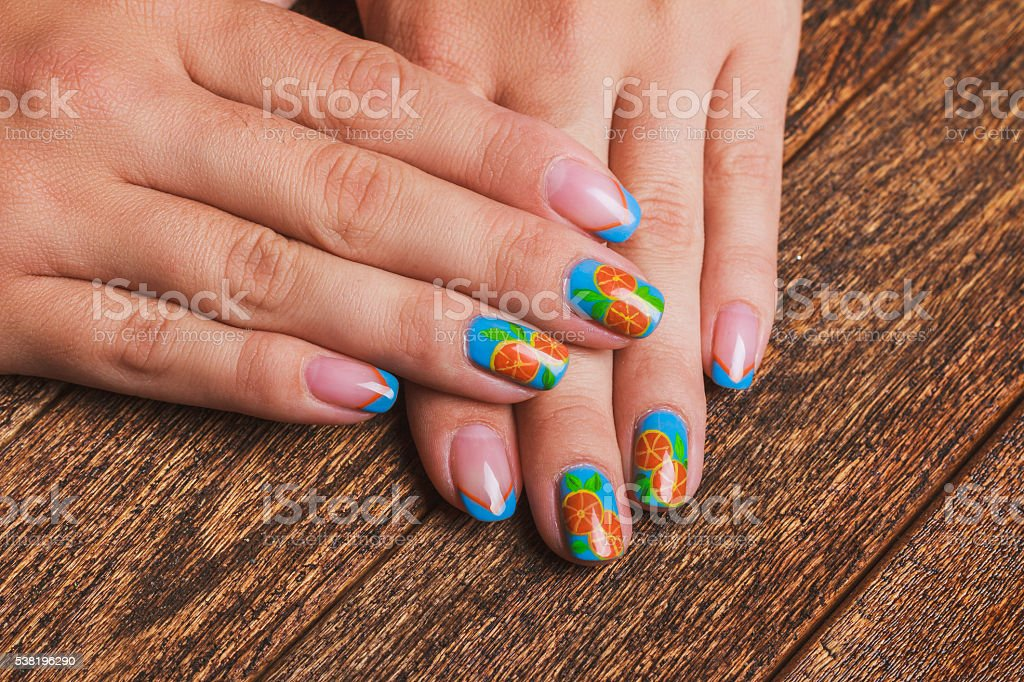 Summer french blue nail art with painted orange fruit stock photo