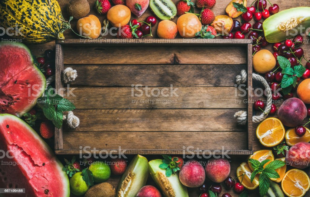Summer fresh fruit variety with rustic wooden tray in center stock photo