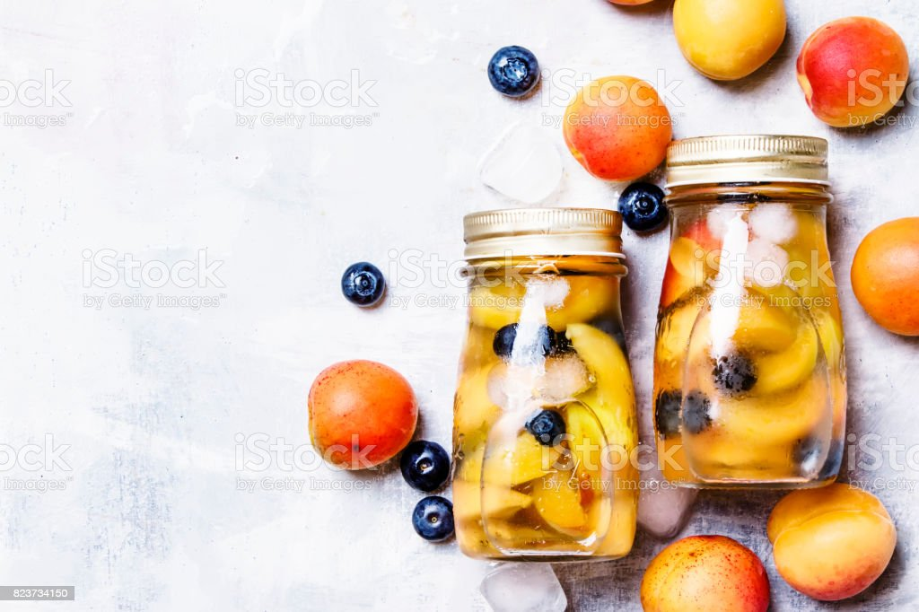 Summer fruit drink with apricot, blueberry and ice