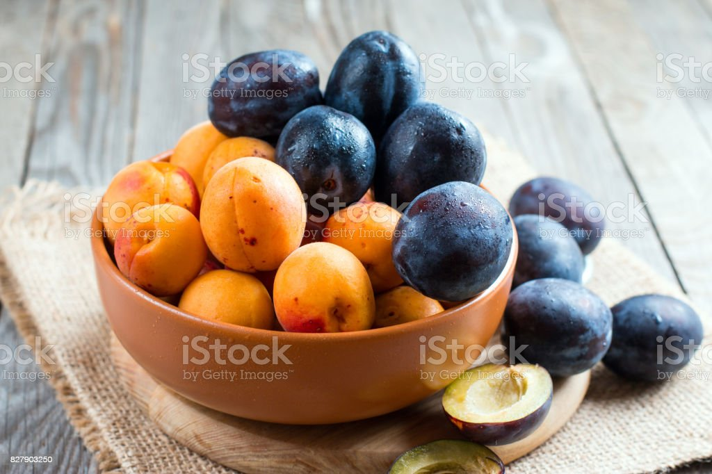 Summer fruits - plums and apricots in a bowl on wooden background stock photo