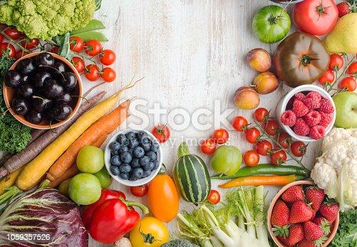 Fresh farm produce, summer fruits vegetables berries, cherries strawberries raspberries broccoli cauliflower squash tomatoes carrots beans, pepper, copy space, top view, selective focus