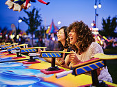 Two young women having fun and playing games at a summer carnival midway.