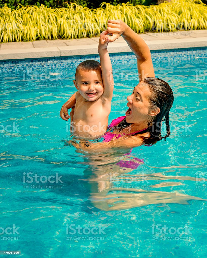 Summer fun for mother and son in the backyard pool. Mom is helping...