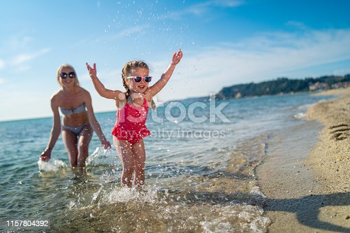 Smiling mother and her daughter are splashing themselves in the sea.