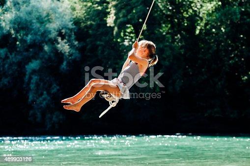 Little girl having fun on rope swing above river.