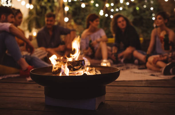 Summer fun Group of happy young people sitting around fire and having fun. bonfire stock pictures, royalty-free photos & images