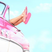 Summer fun vintage car. Legs showing from pink vintage retro car. Freedom, travel and vacation road trip concept lifestyle image with xwoman and copy space on blue sky.