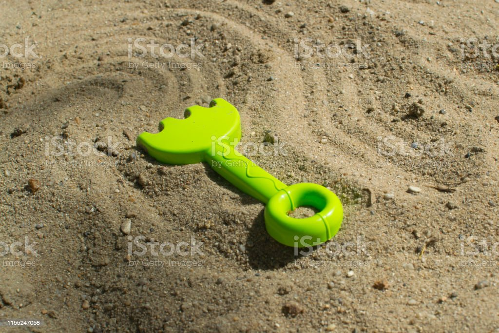 Summer games in the sandbox with green rakes sunny day close up