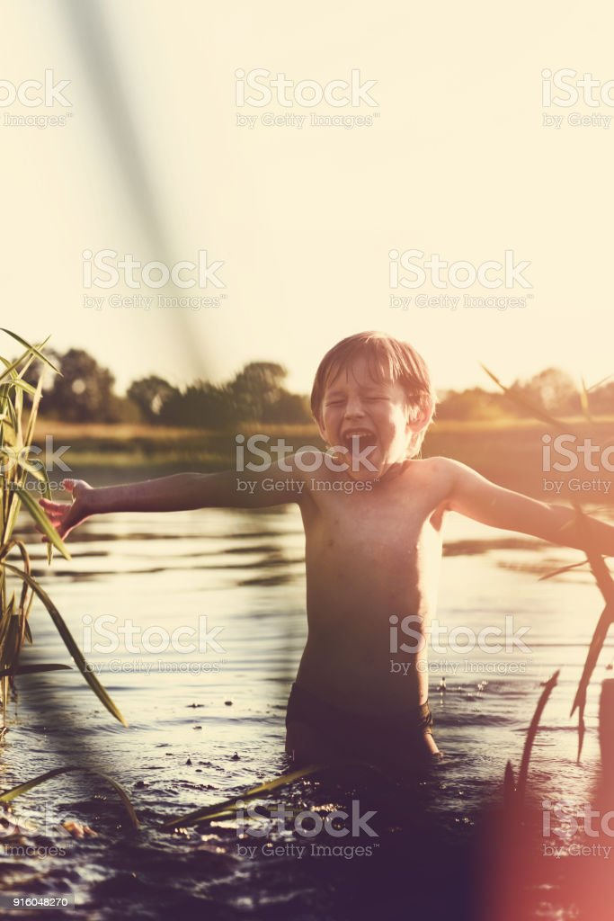 Little boy play in water and making splash