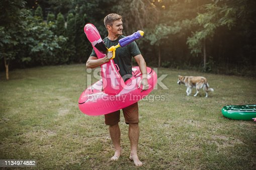 Young man and his dog on vacation in countryside, they enjoy in summer nature. They play with water guns and float