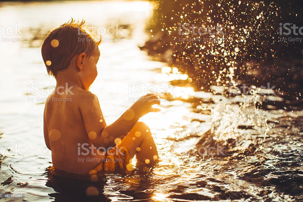 Portrait of a little boy bathing in the river, splashing and playing...
