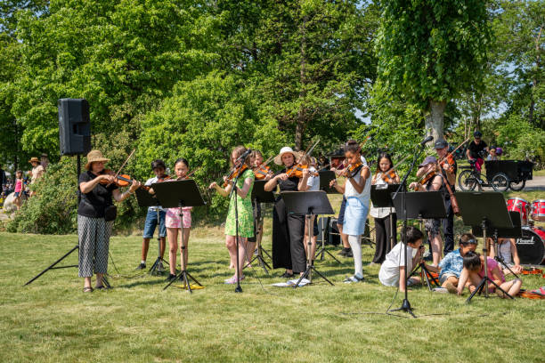 Summer garden front view of adults and young people in an orchestra with instruments playig classical music together. stock photo