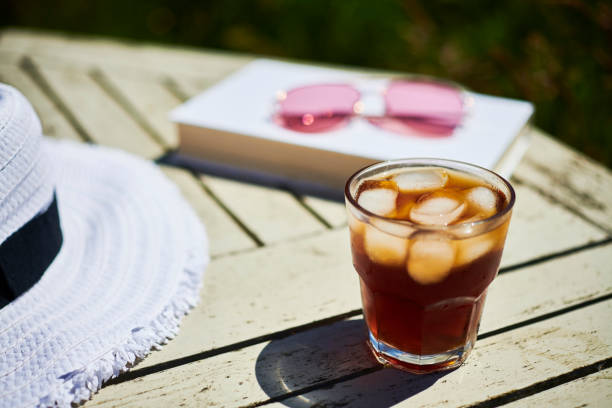 summer garden scene, glass of black iced coffee on a garden table in bright sunshine. - iced coffee stock pictures, royalty-free photos & images