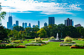 A large garden scene with plants and a fountain in Lincoln Park Chicago with the city skyline