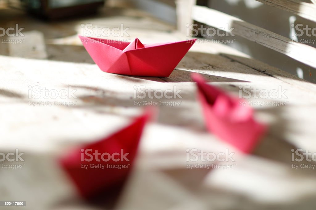 Red origami paper ships on a wooden garden bench in the sun.