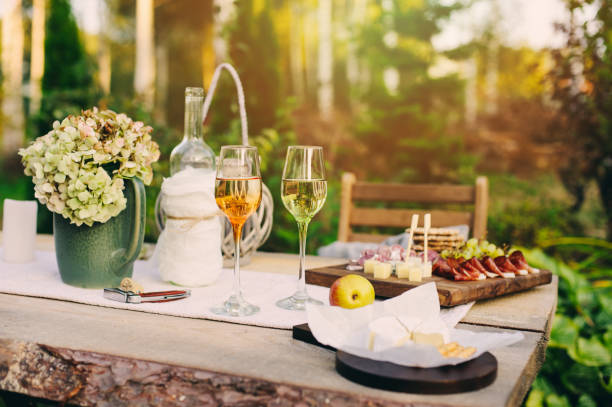 summer garden table decorated with flowers and candles, evening party with wine, cheese and fruits stock photo