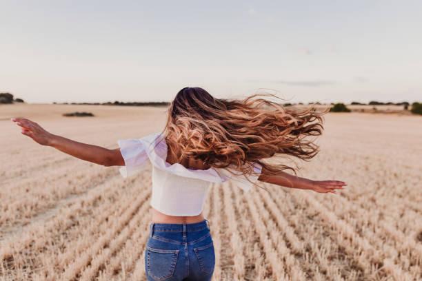 summer girl curtindo a natureza no campo amarelo. linda jovem dançando ao ar livre. cabelo comprido ao vento. felicidade e estilo de vida. vista de trás - longo - fotografias e filmes do acervo