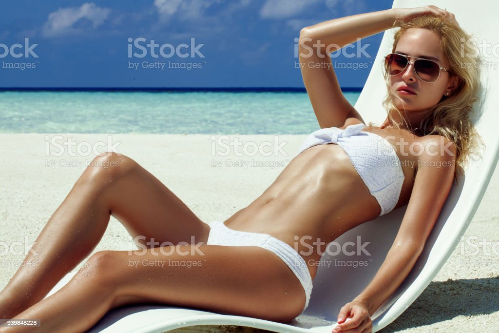 Summer girl model with tanned sexy body. Posing in the white chair on the beach of the tropical island stock photo