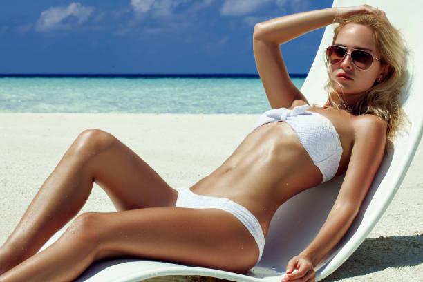 Zomer meisje model met gelooid sexy lichaam. Poseren in de witte stoel op het strand van het tropische eiland foto
