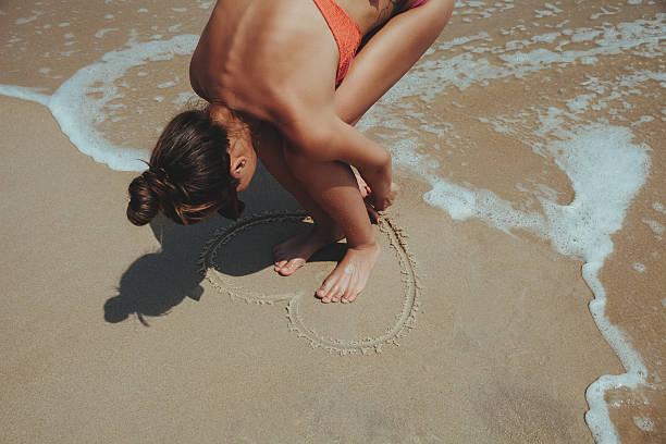 Sommer Mädchen Meer. Jugendlicher machen Herz auf Sand. – Foto