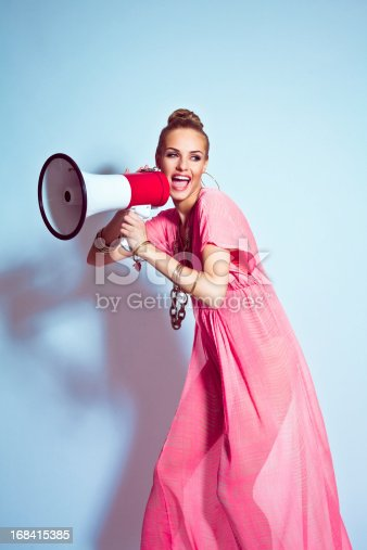 Smiling, beautiful young blond woman wearing pink, summer dress and gold  jewellery shouting into megaphone. Studio shoot, blue background. Summer portrait.