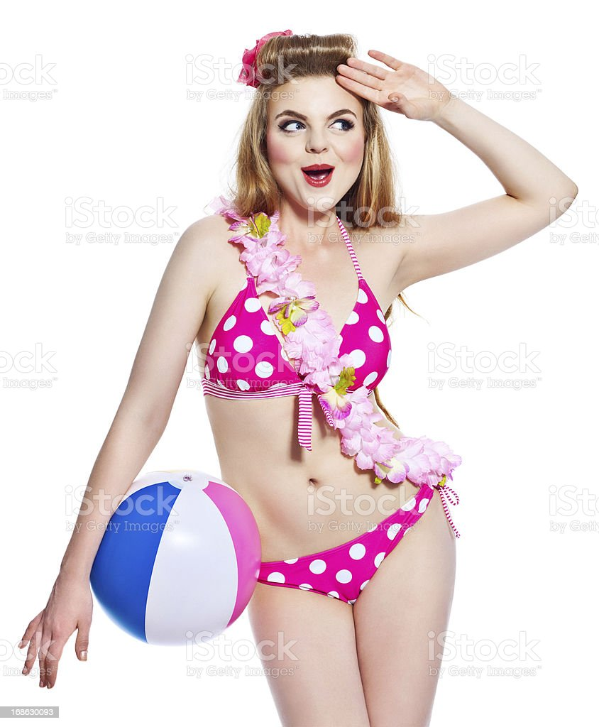 Summer Girl, Studio Portrait Summer portrait of sensual young woman wearing bikini and flower garlands, holding a beach ball and saluting. Studio shot on white background. 18-19 Years Stock Photo