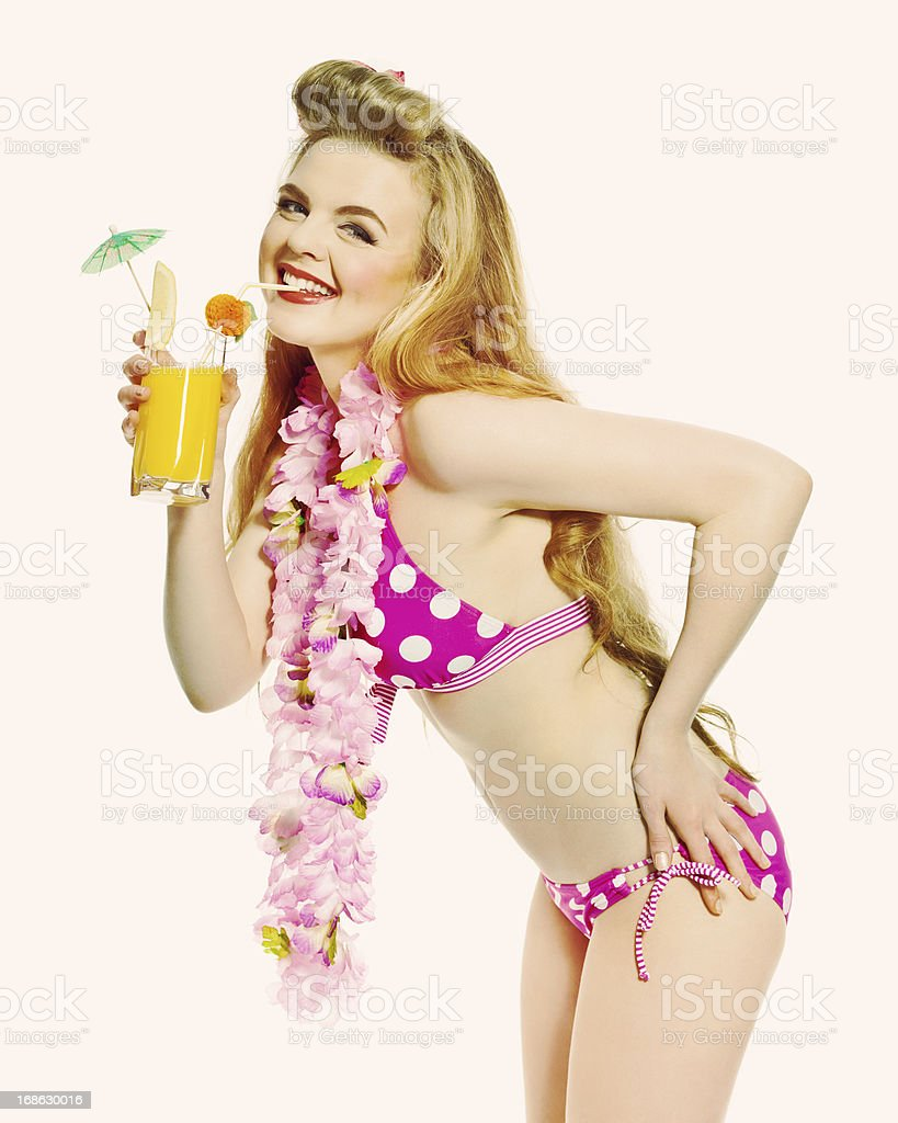 Summer Girl with Orange Juice, Studio Portrait Portrait of excited young woman wearing bikini and flower garlands, drinking orange juice in hand and smiling at the camera. Studio shot on white background. 18-19 Years Stock Photo