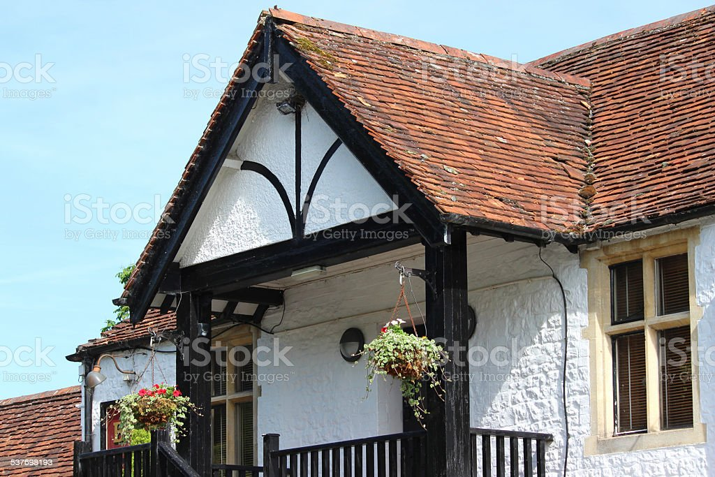 Summer hanging baskets with flowers, outside white house in country stock photo
