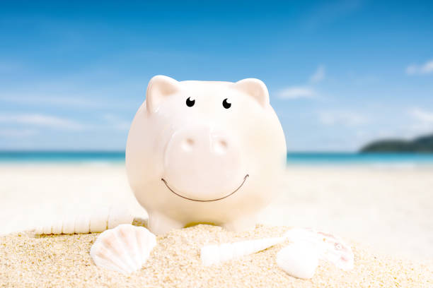summer happy piggy bank on sand beach over blurred tropical blue sea background. stock photo