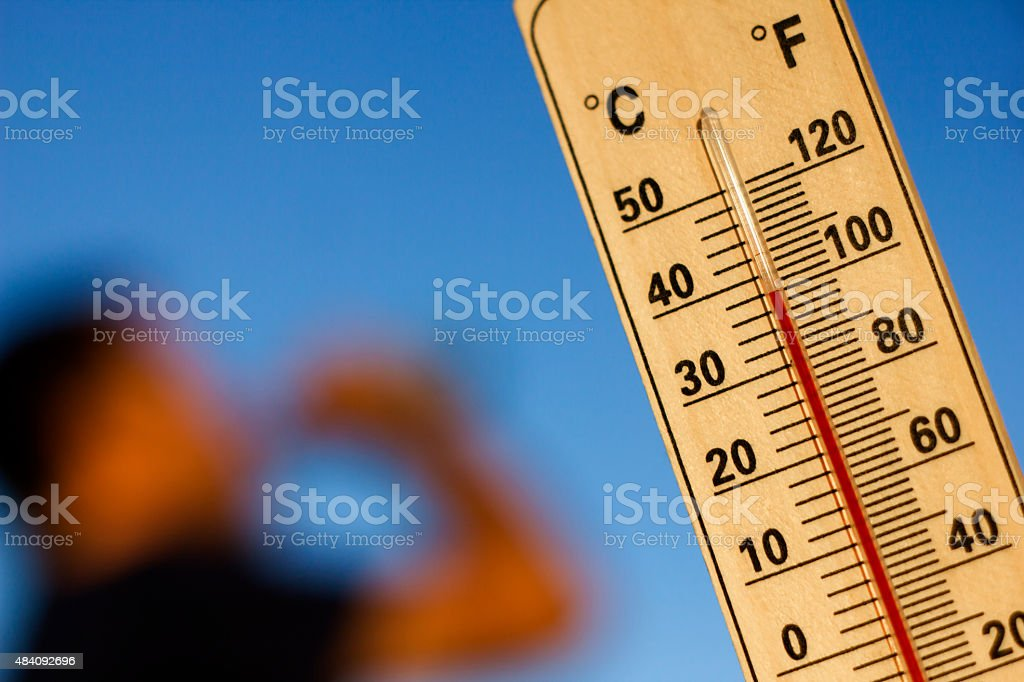 thermometer with 100 degree Fahrenheit and in background man...
