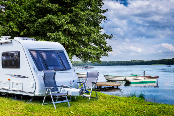 Summer holiday at the lake, Masuria, Poland Camping trailer on the lake shore, Masuria, Poland trailer park stock pictures, royalty-free photos & images