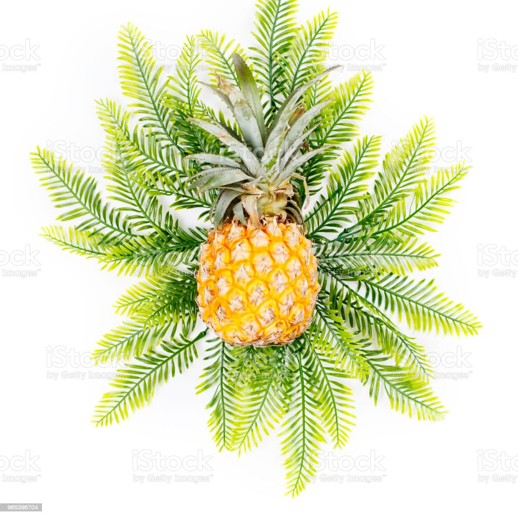 Summer holiday background. Tropical plant leaves and pineapple on yellow background. Flat lay royalty-free stock photo